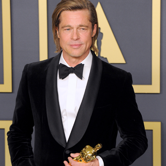 Brad Pitt clutching his Oscar backstage after his Best Supporting Actor win