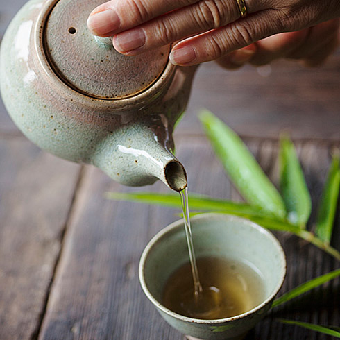 Green tea being poured into handle-less cup from ceramic teapot
