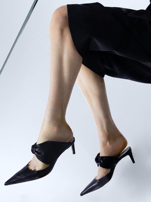 Black leather kitten heels with exaggerated bow details