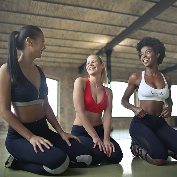Three women laughing after a workout