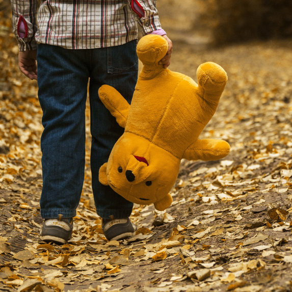 A kid holding an upside down Winnie the Pooh stuffed animal, surrounded by autumn leaves