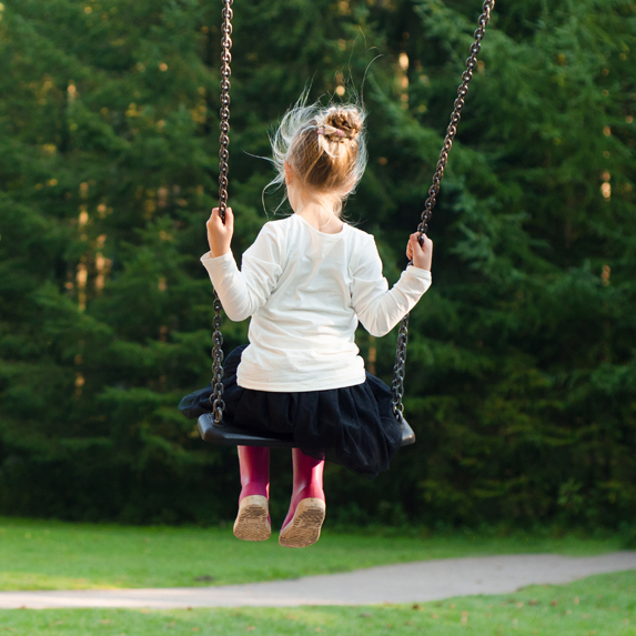 A little girl on a swing wearing rain boots and a dress
