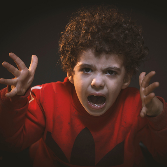 A young boy yelling and gesturing with his hands