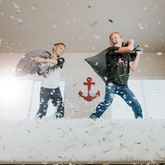 Two kids in the middle of a pillow fight on top of a bed