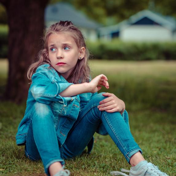 An upset little girl sitting on the grass under a tree