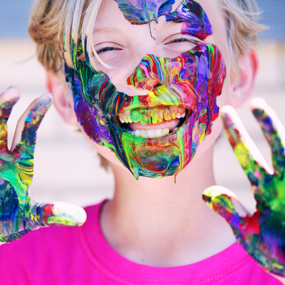 A closeup of a little boy covered in multi-coloured paint