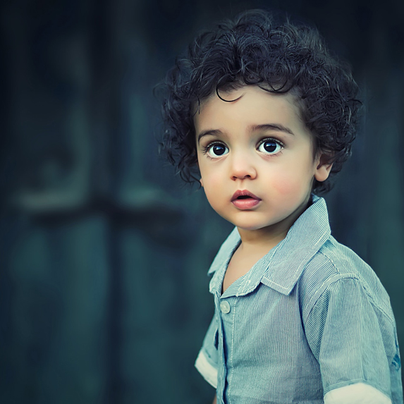 A curly-haired boy walking around outside