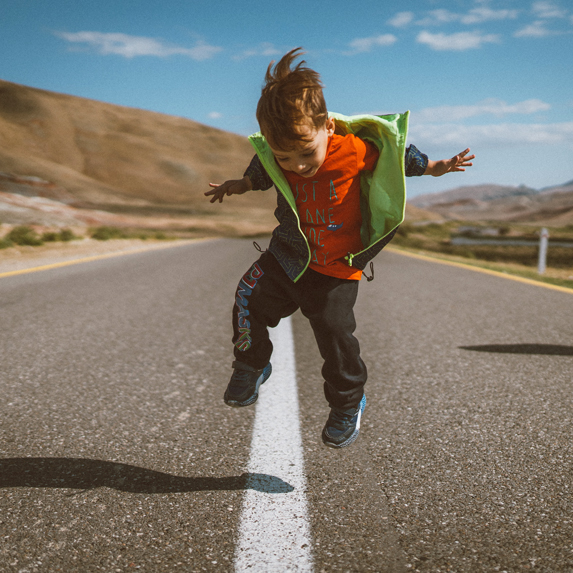 A little boy jumping up and down outside on the side of the road
