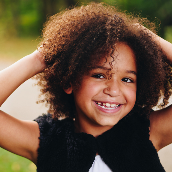 A curly-haired little girl smiling and laughing outside