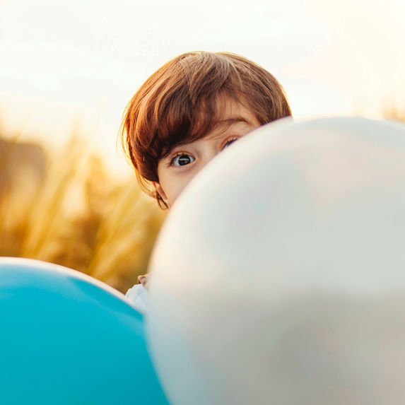 A kid poking their face out from behind two balloons