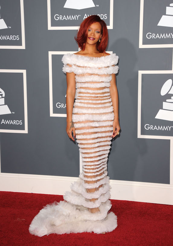 Rihanna wears a sheer-paneled white gown with feather details to the Grammy Awards in 2011