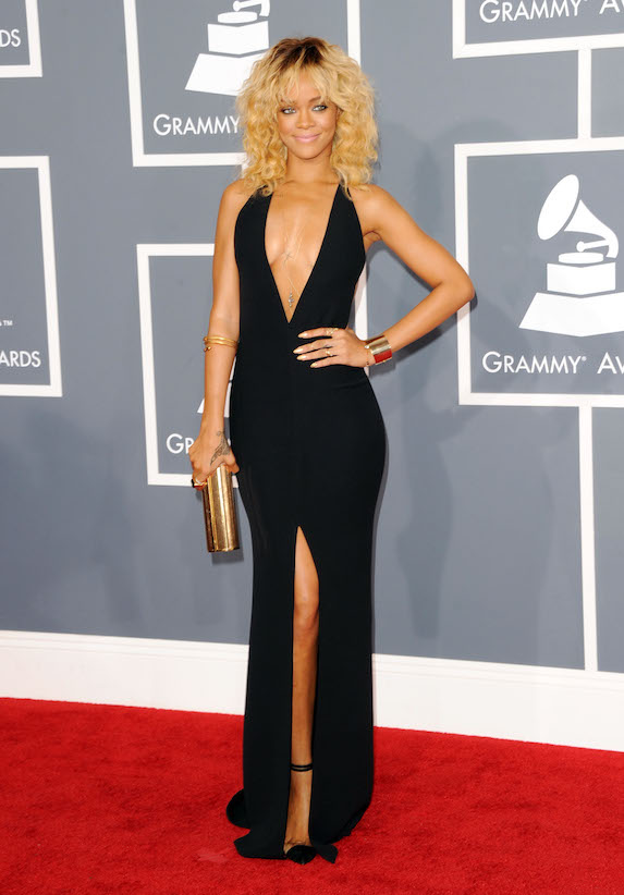 Rihanna wears a black low-cut gown with curly blonde hair at the 2012 Grammy Awards