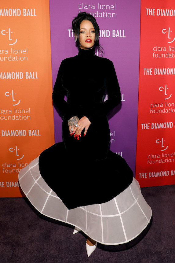 Rihanna wears a black gown with white detail while attending the Diamond Ball in 2019