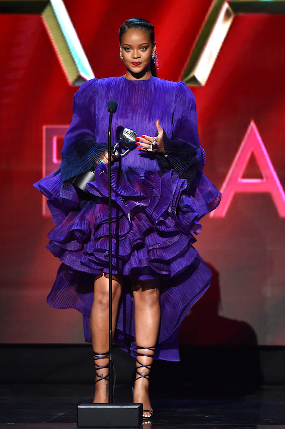 Rihanna wears a purple mini dress on stage while accepting an award in 2020