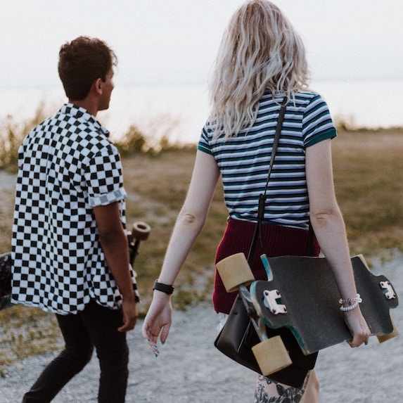 couple walking on a path with a field