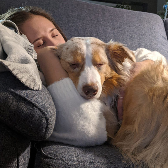 Cute girl and perfect dog nap on a couch