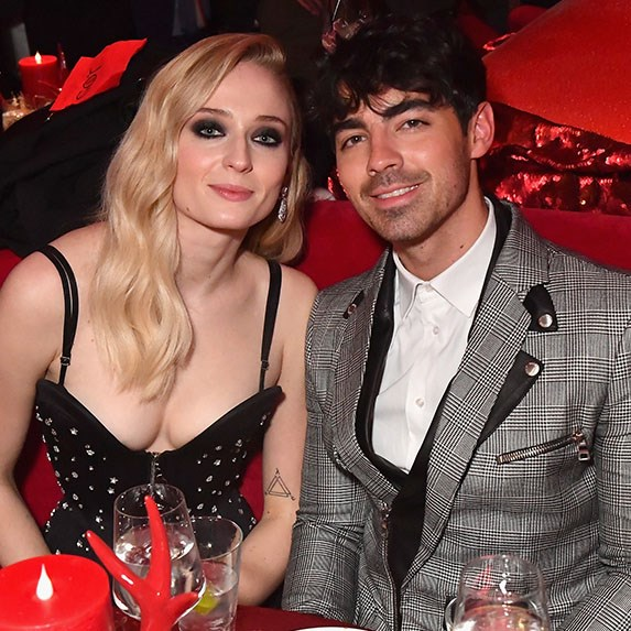 Sophie Turner and Joe Jonas seated at a table, dressed up