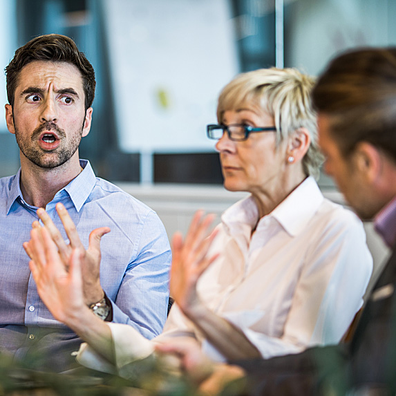 Angry man talking to man while woman sits between them awkwardly