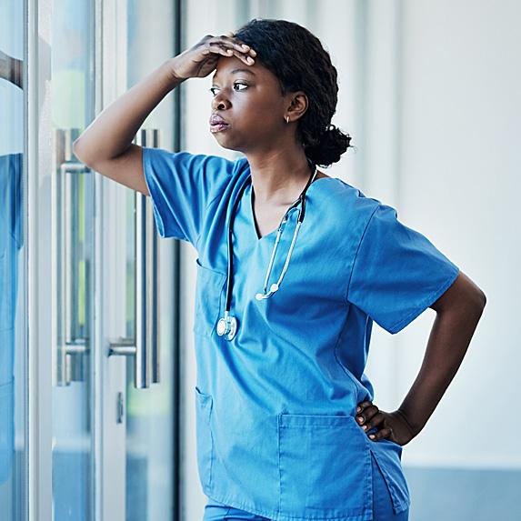 Upset nurse looking out glass doors