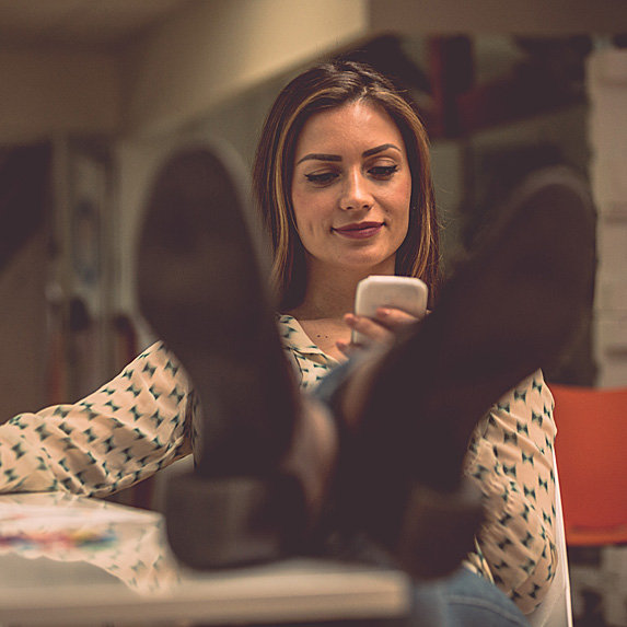 Woman sitting with feet up, looking at phone