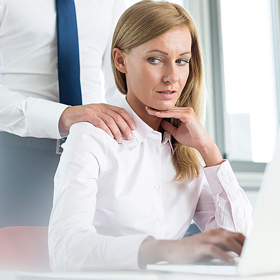 Uncomfortable woman at desk looking at man's hand on shoulder