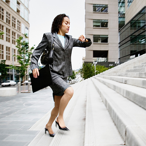 Woman running up steps, looking at watch