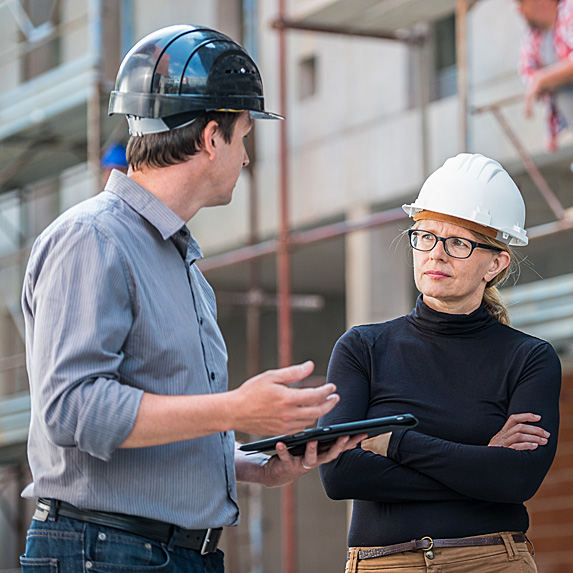 Man and annoyed-looking woman speak at construction site