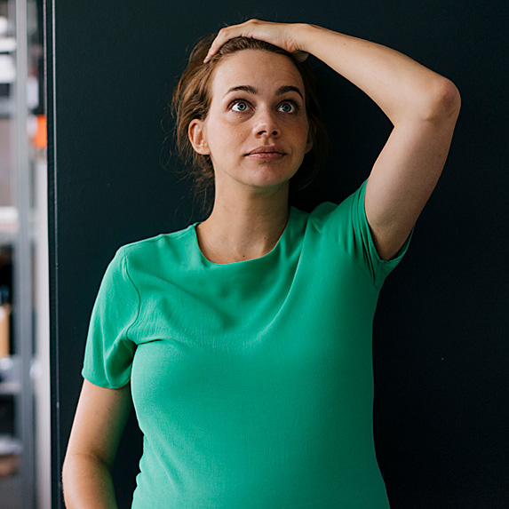 Woman standing outside of warehouse in shock