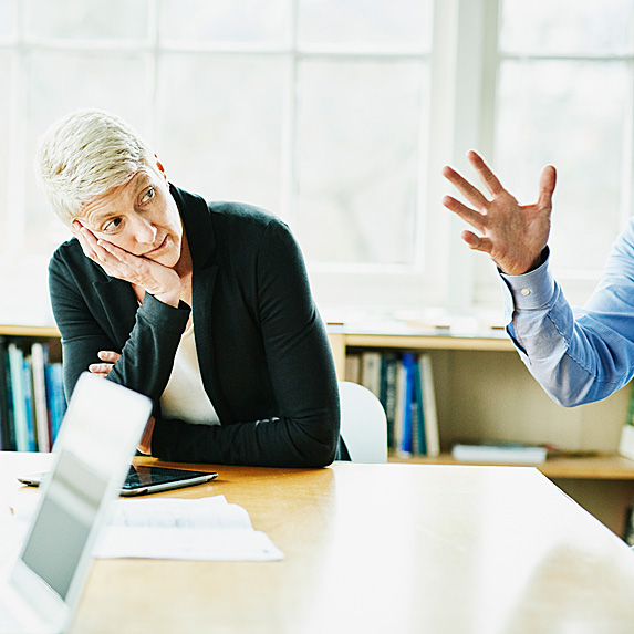 Woman looking on in disbelief as man talks
