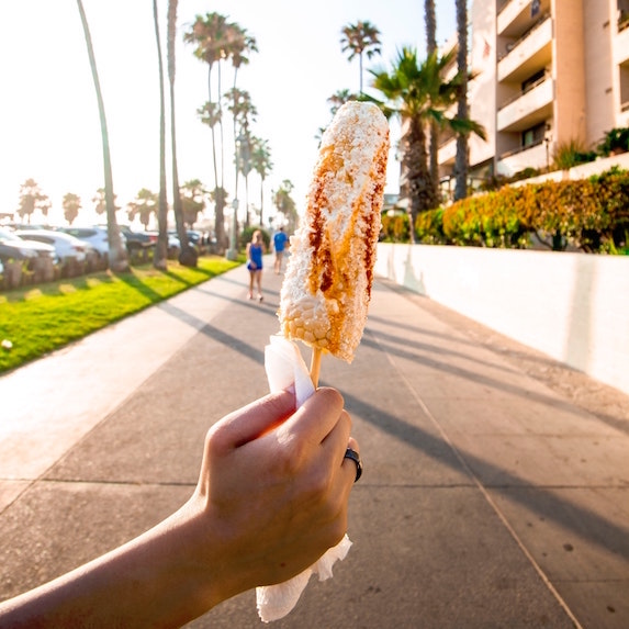 hand holding elote corn on sunny day