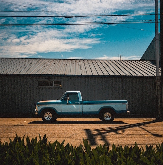 blue and white pickup truck parked outside on sunny day
