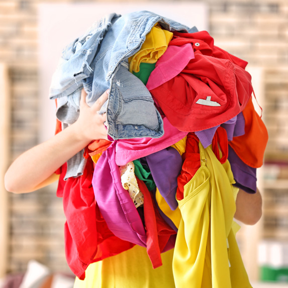 Person holding a pile of clothes
