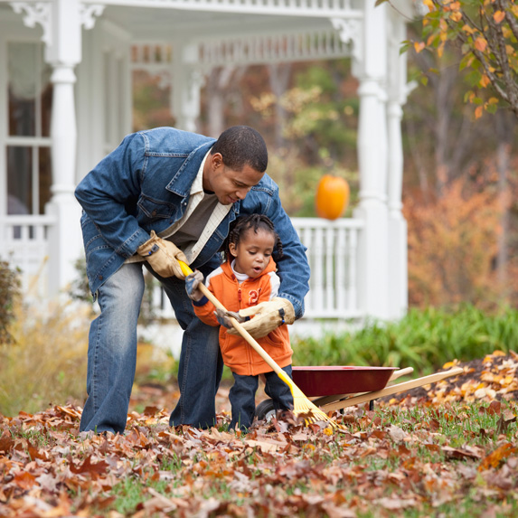 Man and child raking