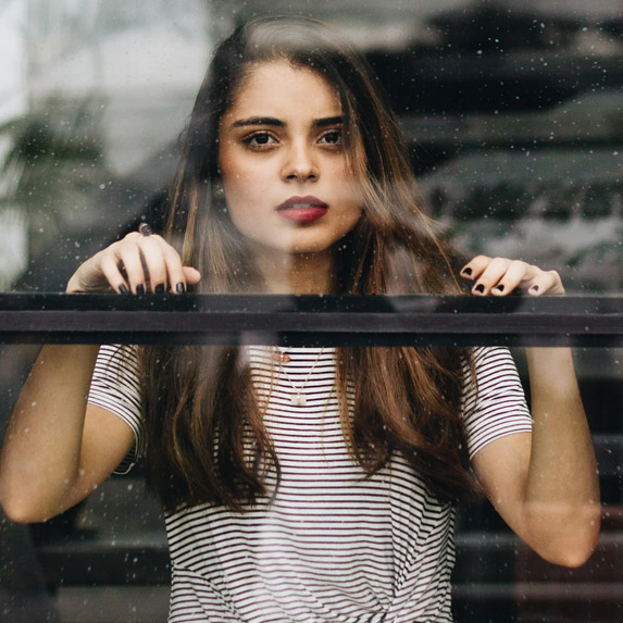 Woman from inside looking through a window to the outside