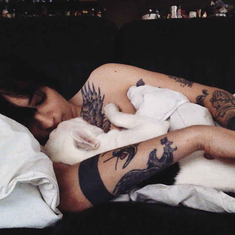 Tattooed woman and her French bull dog sleeping together