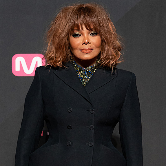 Janet Jackson standing dressed up in a suit.