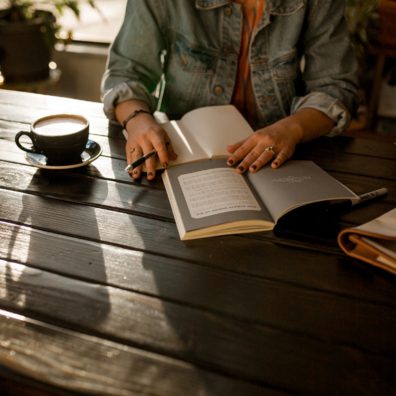 Woman journalling with a cup of coffee and journal