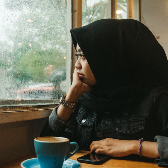 Woman staring out the window at a coffee shop
