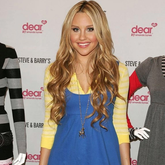 Amanda Bynes standing in a yellow and blue outfit