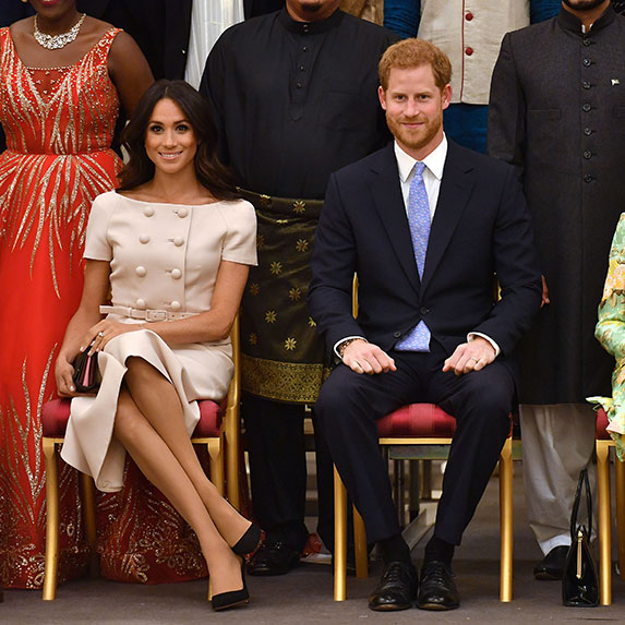 Meghan Markle sits with legs crossed with Prince Harry