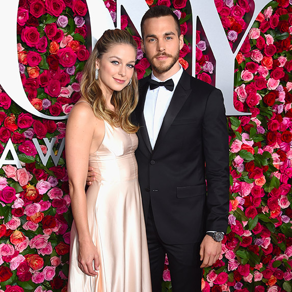 Melissa Benoist and Chris Wood standing in front of a floral wall, in formalwear