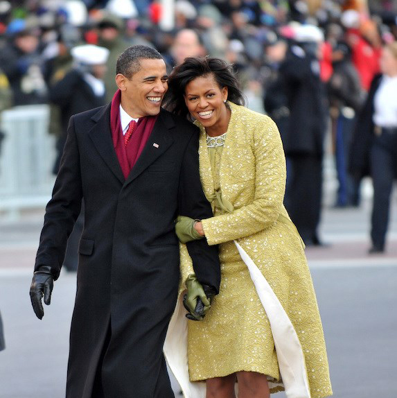 Barack and Michelle Obama walking in winter coats and leaning on each other, laughing