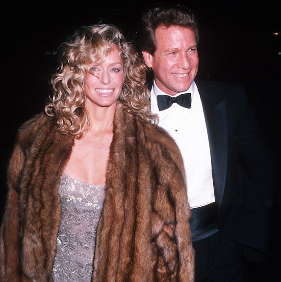 1979: Ryan O'Neal walkign with Farrah Fawcett in eveningwear