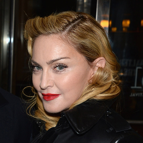 Singer Madonna wearing red lipstick and vintage waves in her hair, looking over her shoulder towards camera.