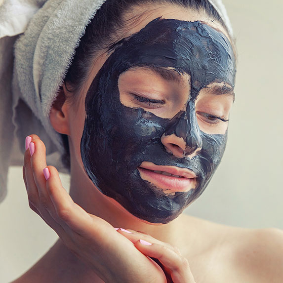 Woman wearing a black face mask and hair towel.