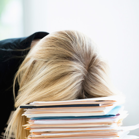 A stressed or tired woman with her head on a stack of folders and files