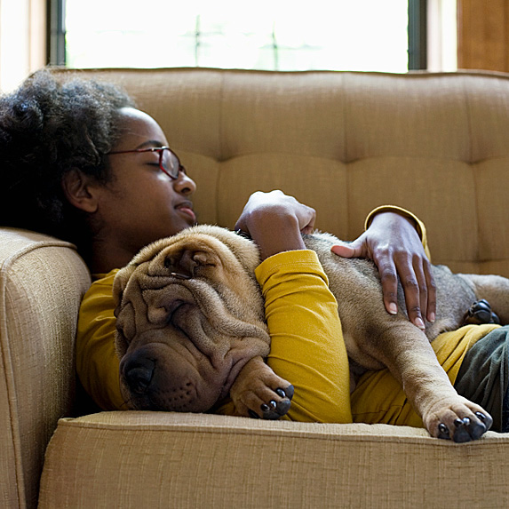 A woman curled up on the couch with her dog