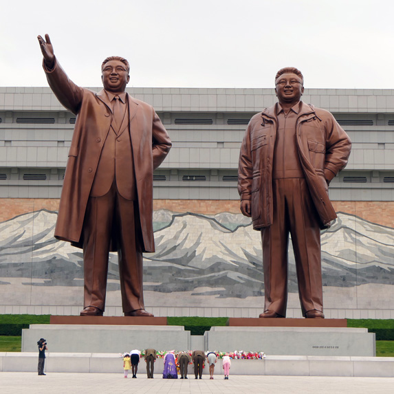 North Korean families in front of statues