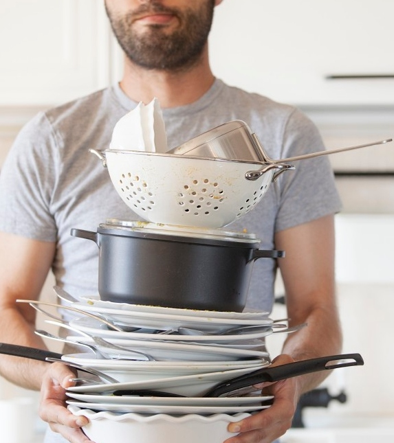 Man holding stack of dirty dishes