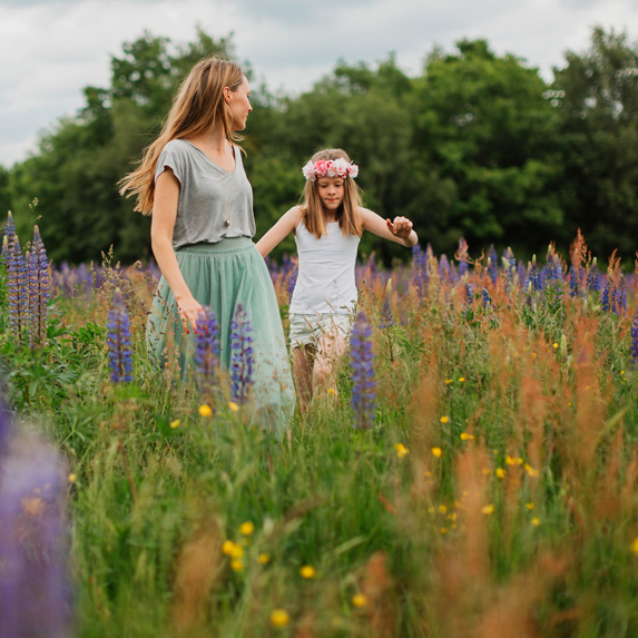 Mother and daughter walking in a meadow